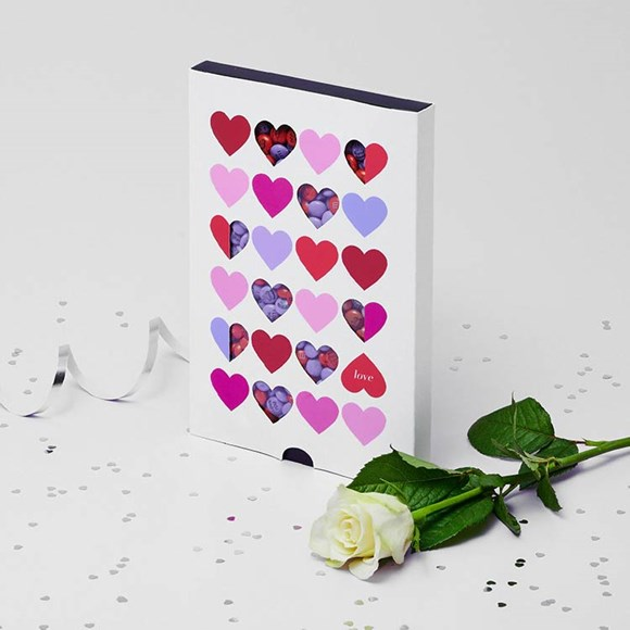 Light purple and red customised M&M'S in a gift box with die-cut windows and heart designs on the front next to a white rose