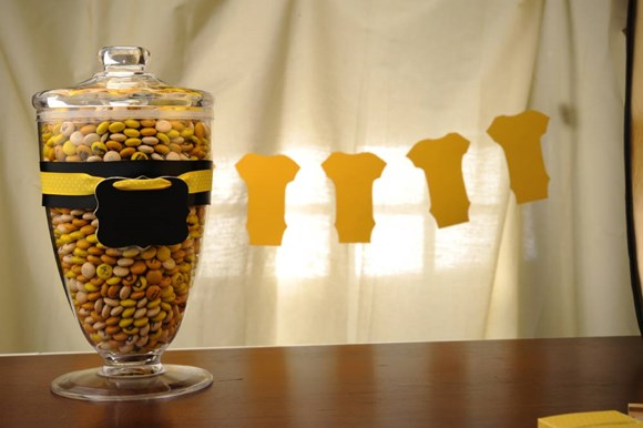 Orange, yellow, and cream customised M&M'S in a decorative glass container with a lid and a black and yellow tag on front
