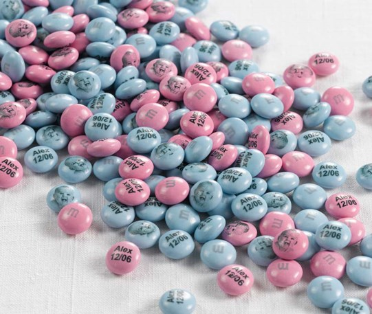 Pink and blue customised M&M'S spilled onto a white background