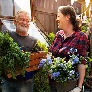 Man and woman outside buying flowers