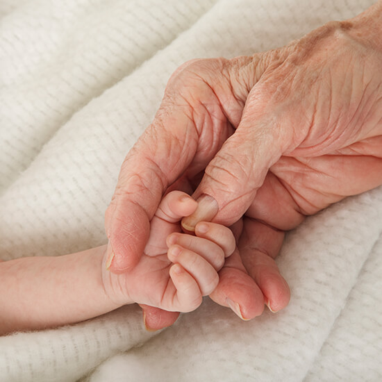 baby and elderly person holding hands