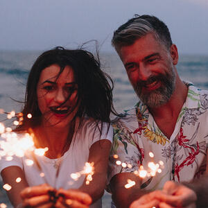 Couple on the beach with sparklers.